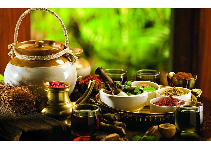 pots, épices et herbes fraiches posés sur une table avec des verres d'eau