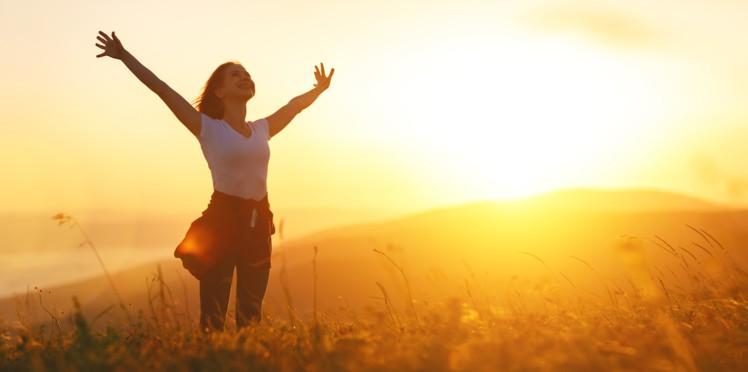 femme qui s'étire les bras en forme de croix dans la nature au couché du soleil