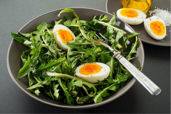 salade de pissenlit dans une assiette avec un œuf dur