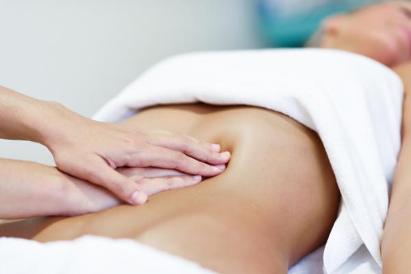 mains posées sur un ventre de femme pour faire un massage