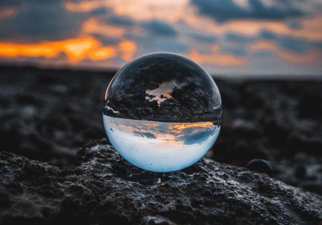bulle d'eau posée sur la terre noire avec le ciel
