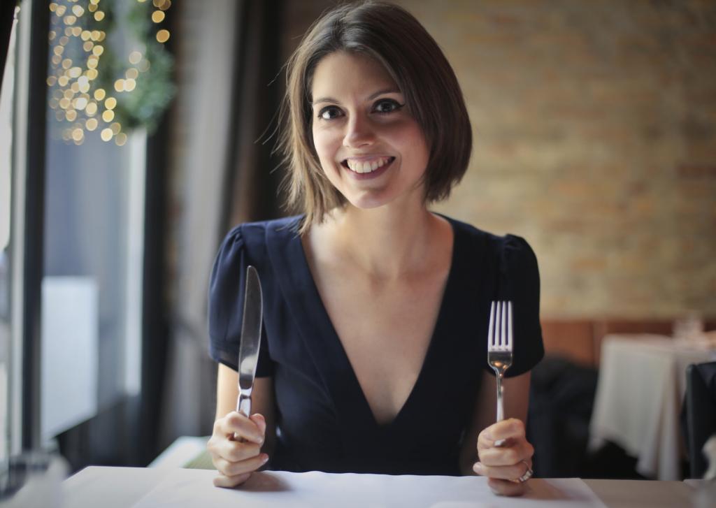 femme à table avec une fourchette et un couteau et qui attend pour manger