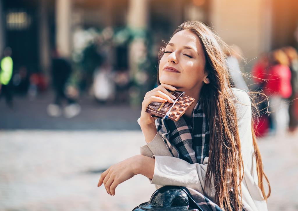 Femme au soleil qui mange du chocolat en fermant les yeux