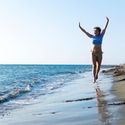 femme qui court sur une plage au bord de l'eau