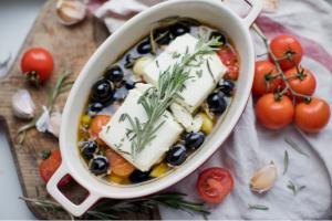 huile d'olive dans un plat avec des olives et de la feta; tomates cerises sur une table