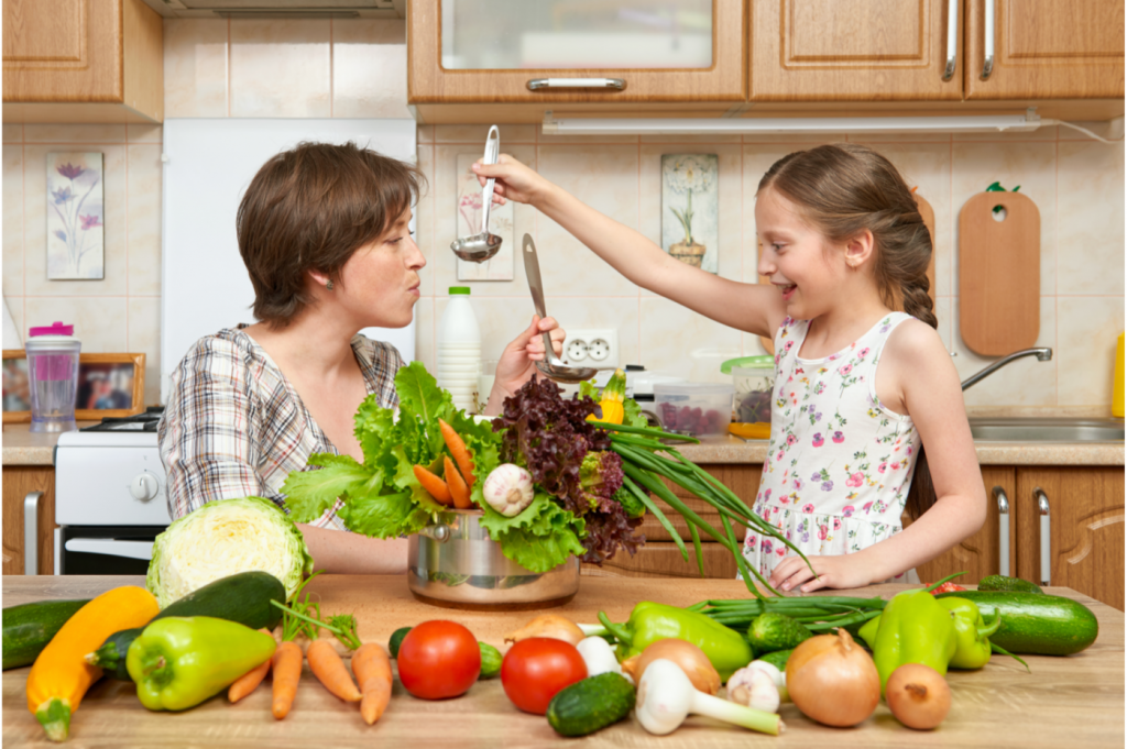 Mère et fille qui cuisine et qui goûte un plat