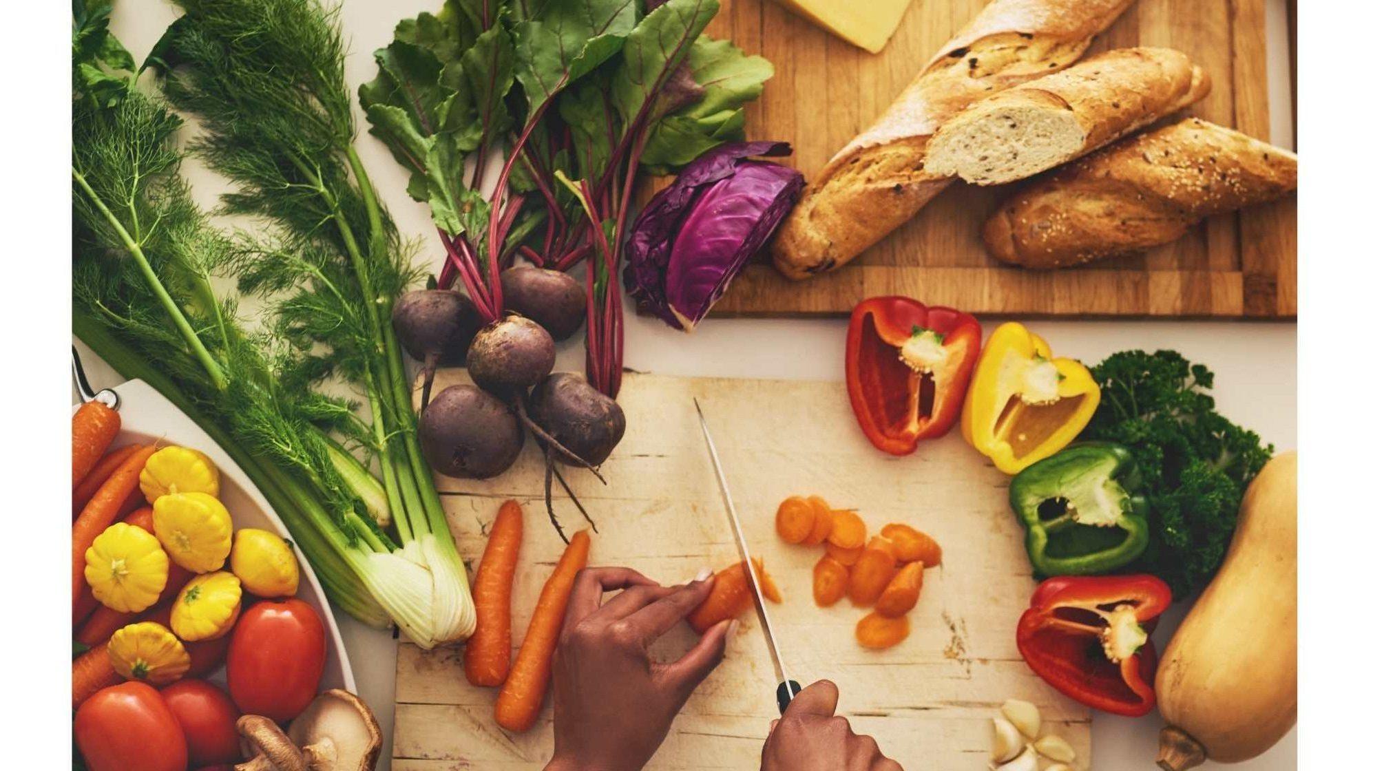 Personne qui prépare le repas. Elle coupe des légumes avec un couteau sur une planche à découpé