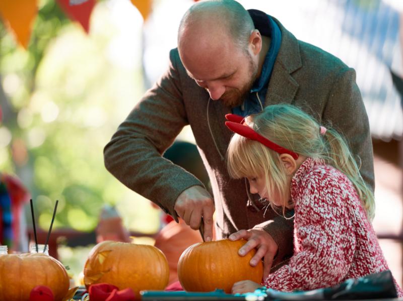 Un père et sa fille qui préparent une citrouille