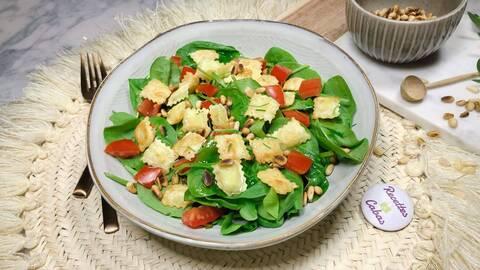 Recette de Salade aux jeunes pousses, ravioles, tomates cerise, jambon cru, pignons